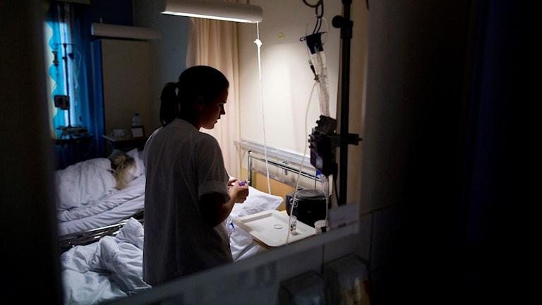 En sjuksköterska syns genom ett fönster in till ett patientrum.