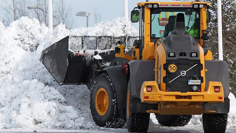 Traktor med skopa vid snöhög