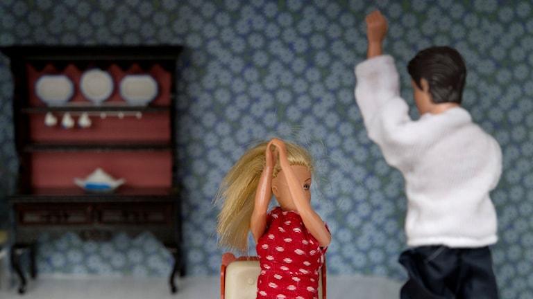 Två dockor i ett dockhus där mandockan avser att slå kvinnodockan.