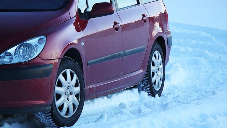 Röd personbil på snöunderlag