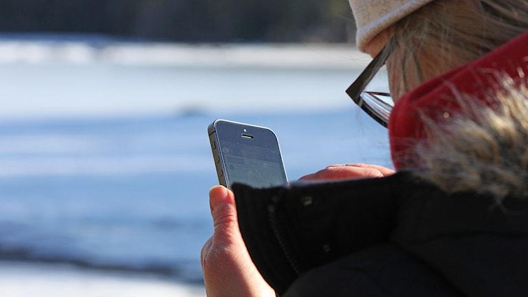 Kvinna håller i mobiltelefon iPhone utomhus vintertid