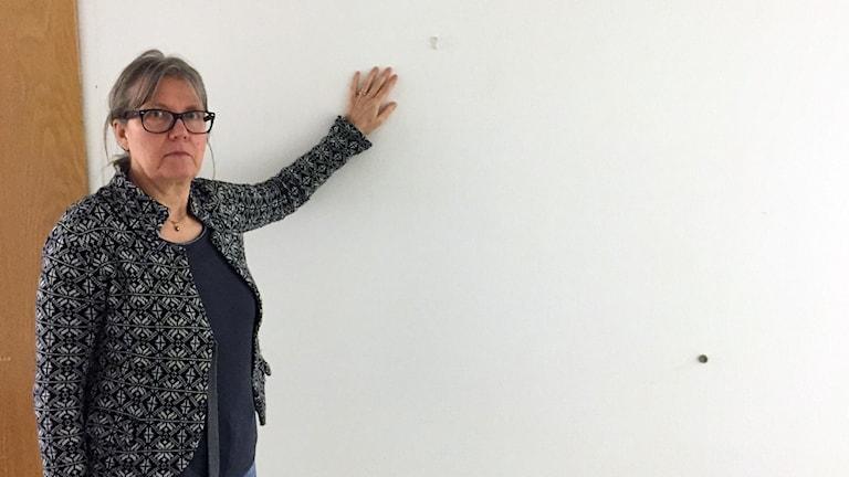 Kvinna står vid en tom vägg och pekar på en tavelkrok där det suttit en tavla som blivit stulen.