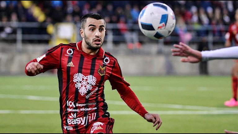 Fotbollsspelare på väg att ta ner en flygande boll