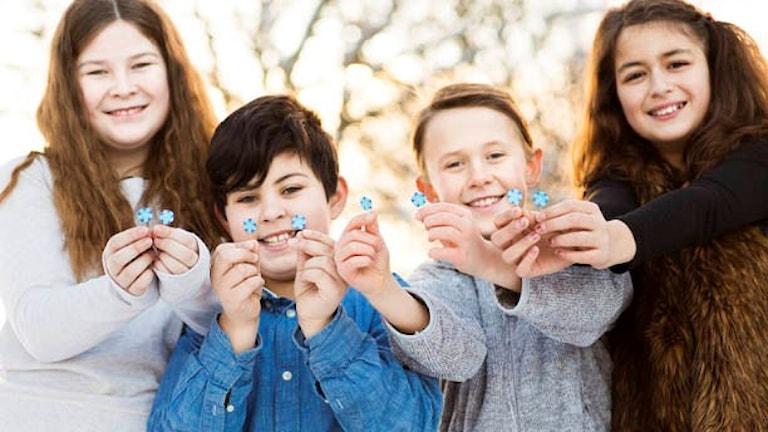 Fyra barn håller upp årets majblomma