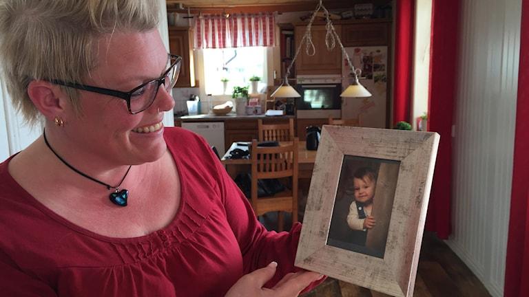 Leende kvinna håller upp ett foto av ett litet barn.