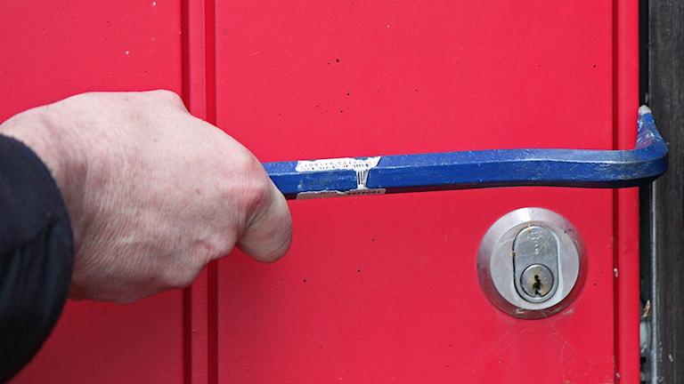 Hand håller kofot vid dörrlås ytterdörr