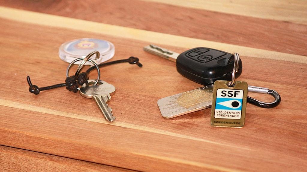 Dörrnyckel och bilnyckel på byrå/bord