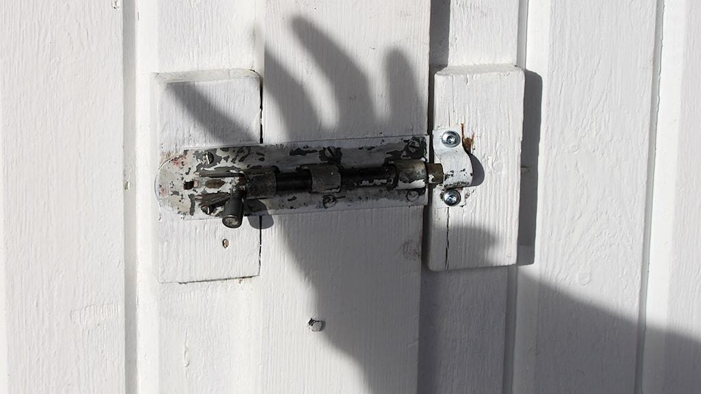 Skugga av hand griper efter dörrlås