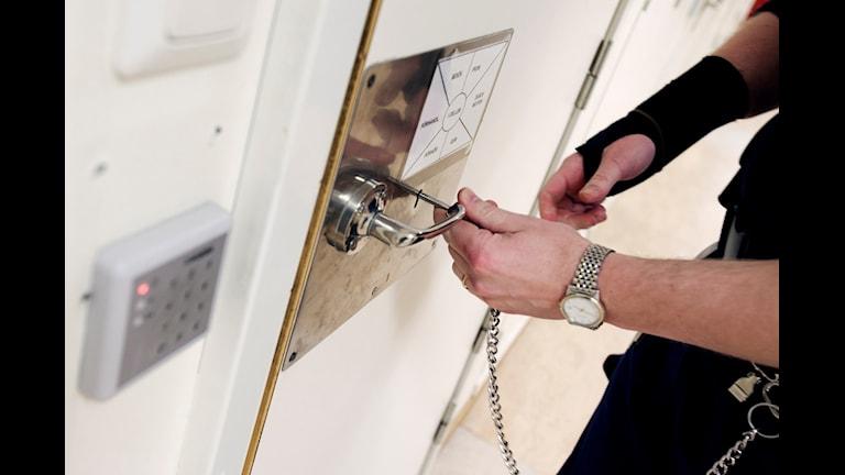 Handen till en uniformerad polis låser dörren till ett häkte.