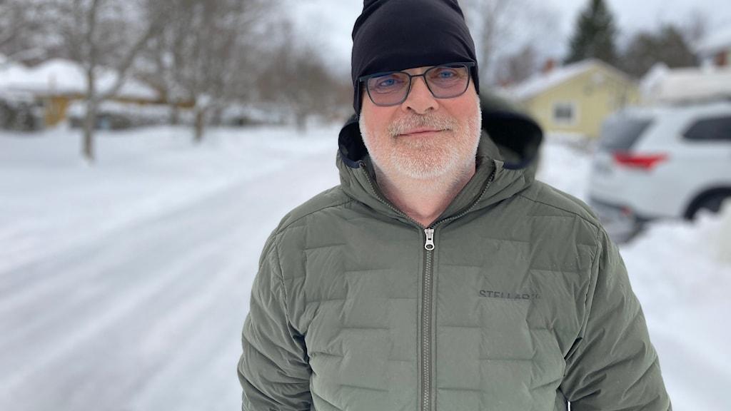 Man med grön vinterjacka och svart mössa. Snölandskap i bakgrunden.