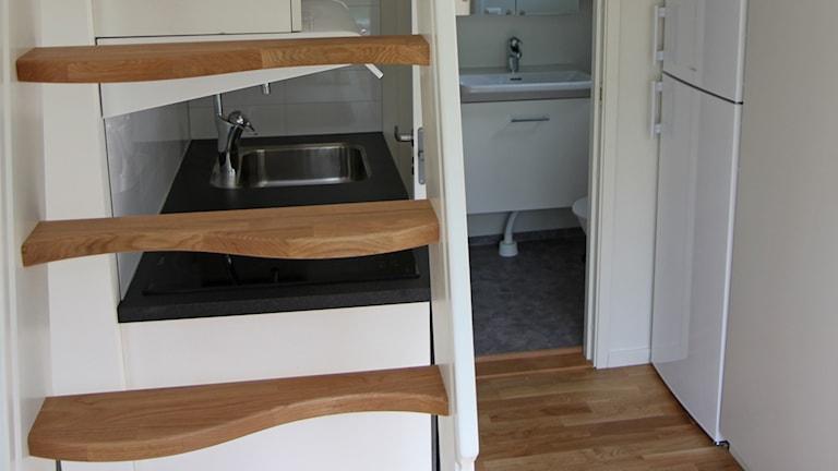 Köksinteriör med trappa, diskbänk kyl- och frysskåp