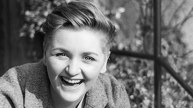 Glad tjej ler mot kameran i svartvitt.