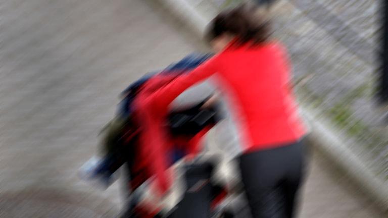 En mamma stressar fram med en barnvagn.
