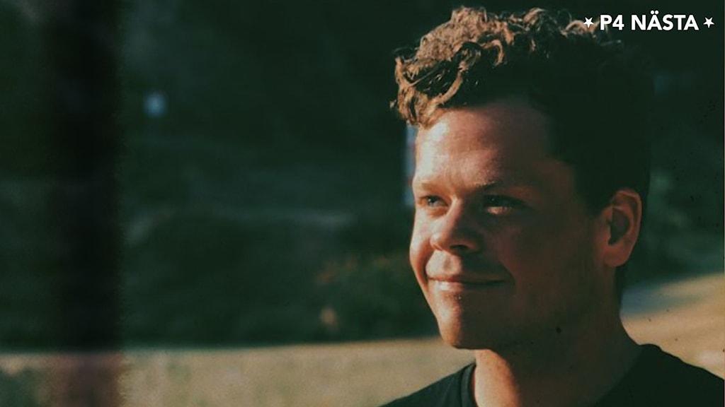 Profilbild leende ung man med kortklippt, brunt, lockigt hår i mörk omgivning