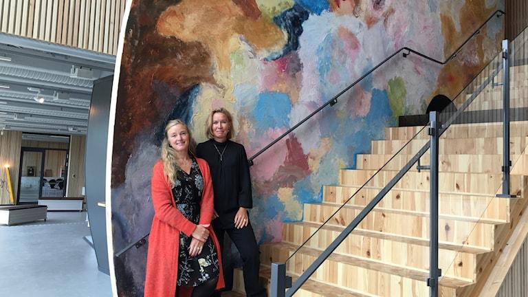 Två kvinnor står i en trappa framför vägg med många olika färger.