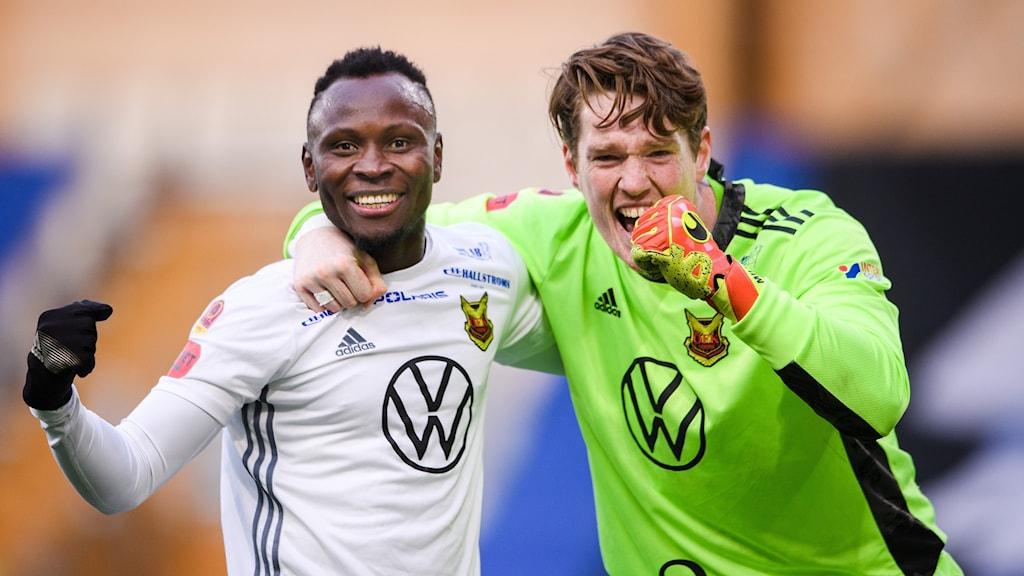 Två manliga fotbollsspelare i vit respektive grön matchdräkt knyter varsin näve och ler
