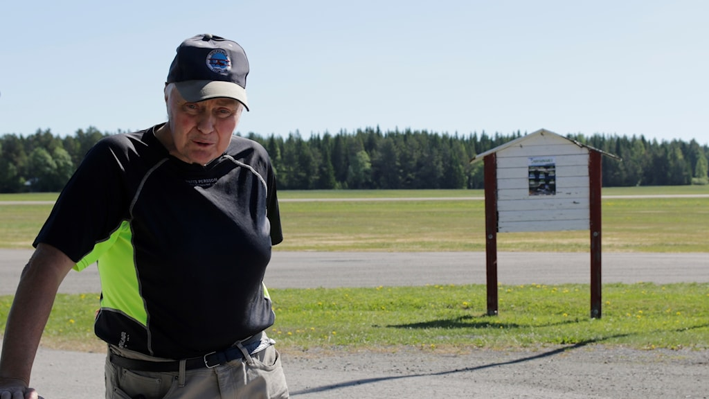 """Bild av äldre man i keps med texten """"östersunds flygklubb"""", bakom honom ett flygfält och soligt väder"""