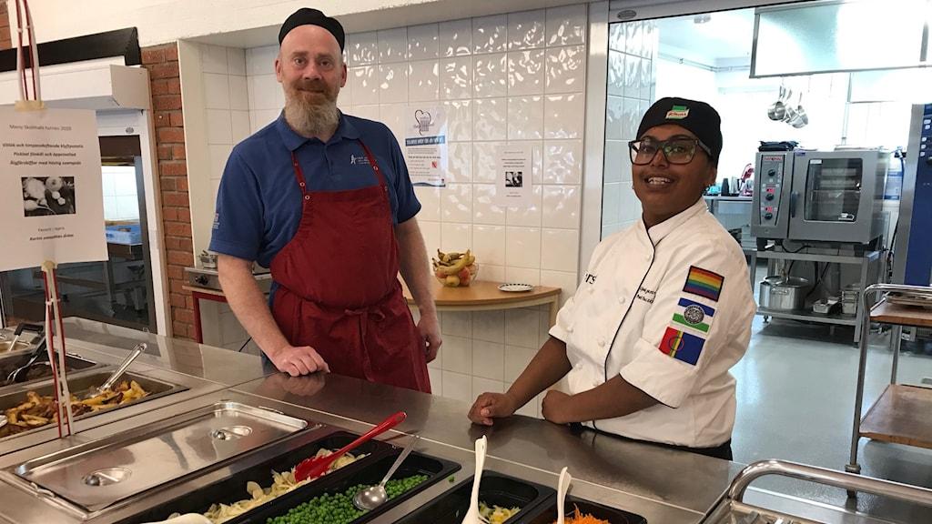 Man och kvinna i förkläden och mössor står vid matservering i skolmatsal