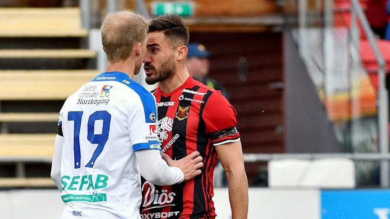 Två fotbollsspelare i dispyt, står med ansiktena mot varandra