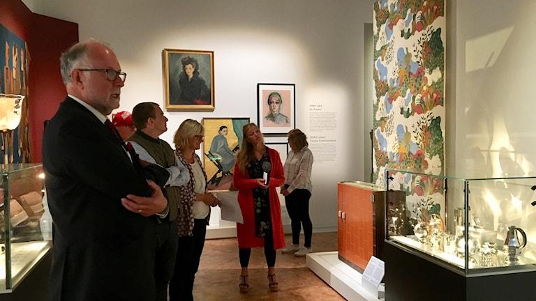 Flera personer står och tittar på konst under en utställning.