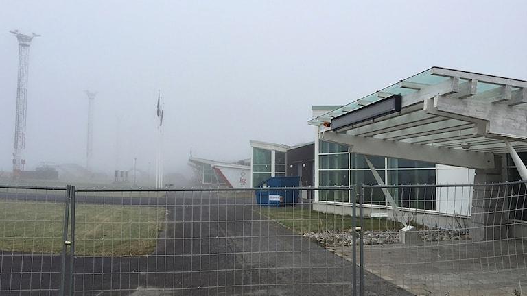 Flygplatsbyggnad insvept i dimma