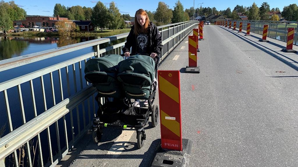 kvinna med bred barnvagn på smal bil-bro