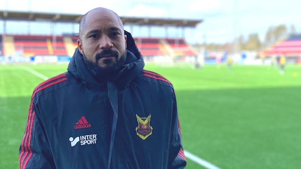 en man som ser ut att frysa i rödsvart jacka med Östersunds Fotbollsklubbs logga på bröstet. Flintskallig och mörkt skägg