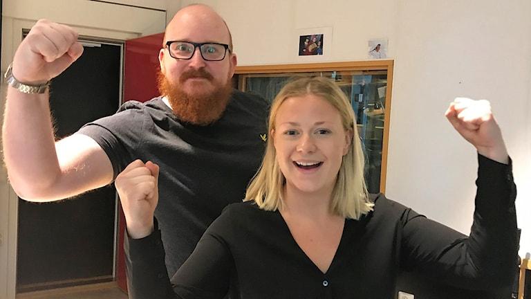 Man med rakat huvud, glasögon och rött skägg och ung blond kvinna spänner sina båda armar i luften