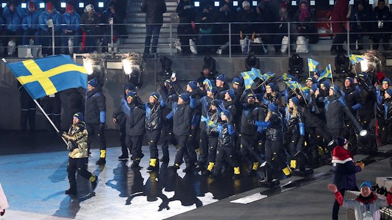 Idrottspersoner går in i blåa kläder och längst fram håller en man upp svenska flaggan.