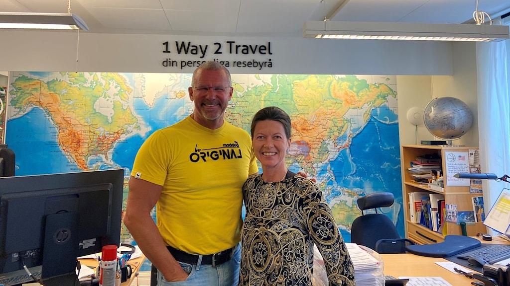 En man och en kvinna som ler och står framför en världskarta.