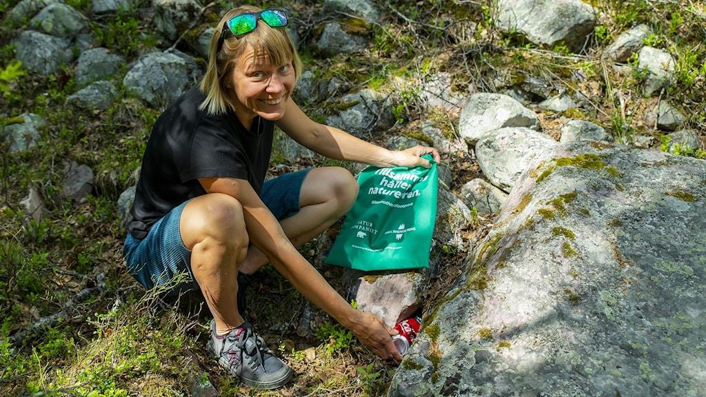 Kvinna med shorts och solglasögon på huvudet plockar skräp i grön påse i fjällmiljö