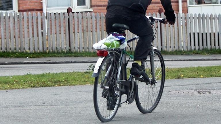 Manlig cyklist färdas på cykelväg i stadsmiljö