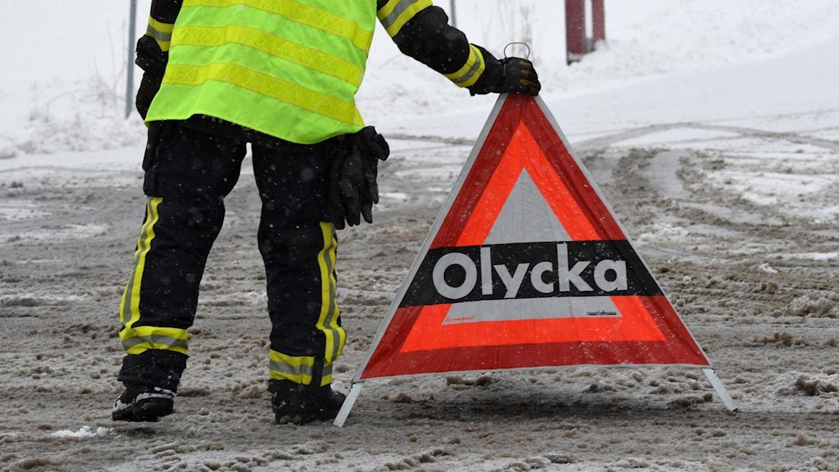 Man i räddningskläder håller i skylt med texten Olycka på snötäckt väg