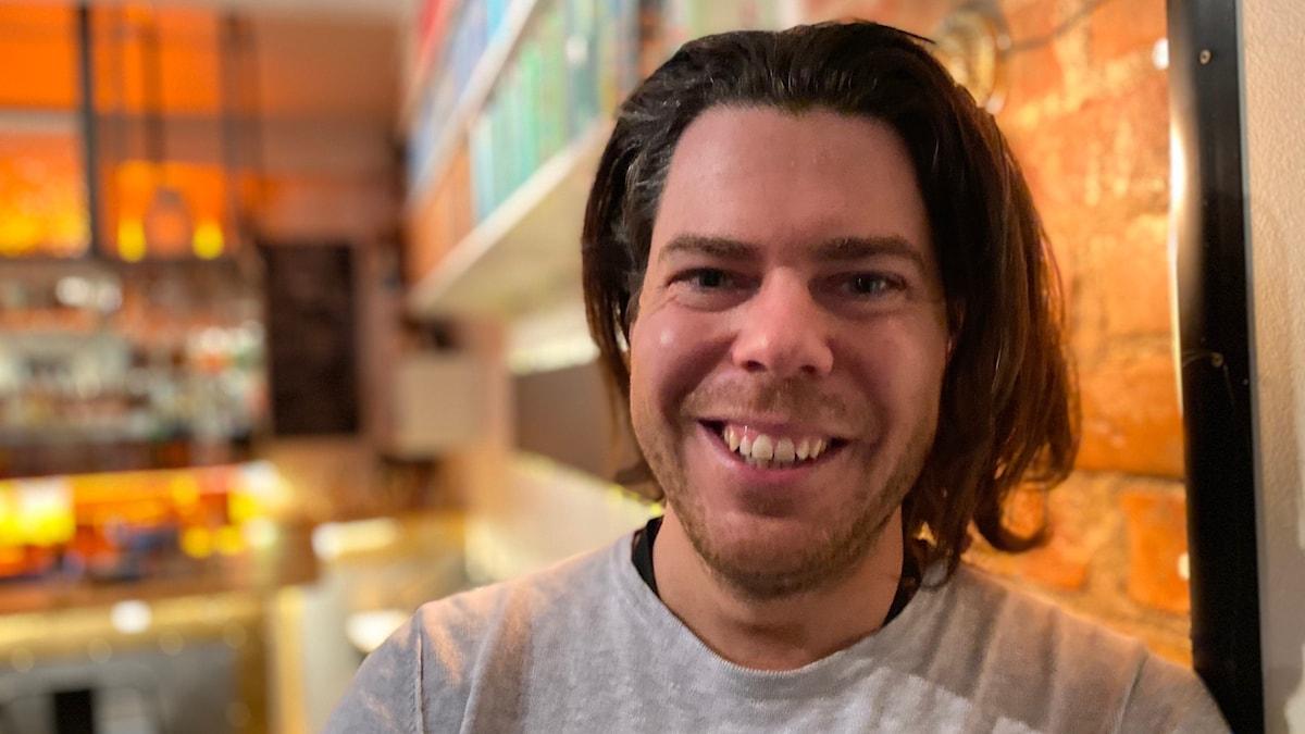 En man i 35-årsåldern med långt brunt hår och grå tröja står lutad mot en tegelvägg.
