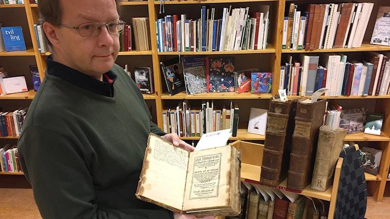En man står och håller i en gammal bok