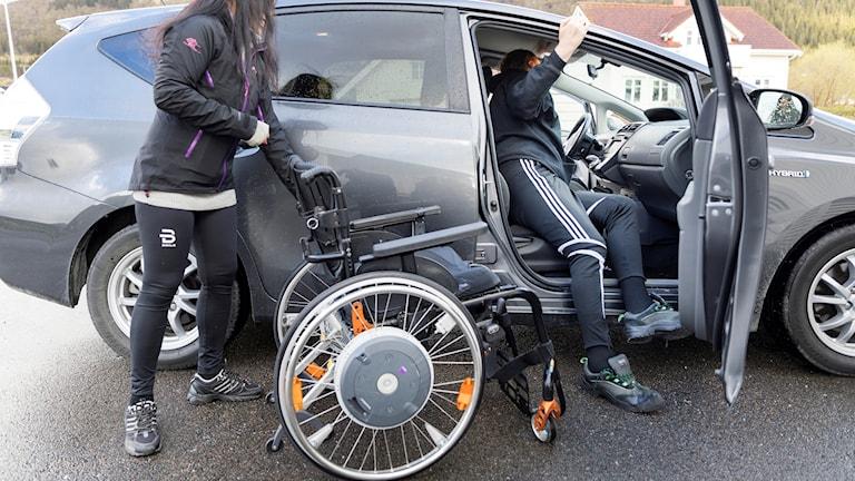 En funktionshindrad kliver in i bil från rullstol.