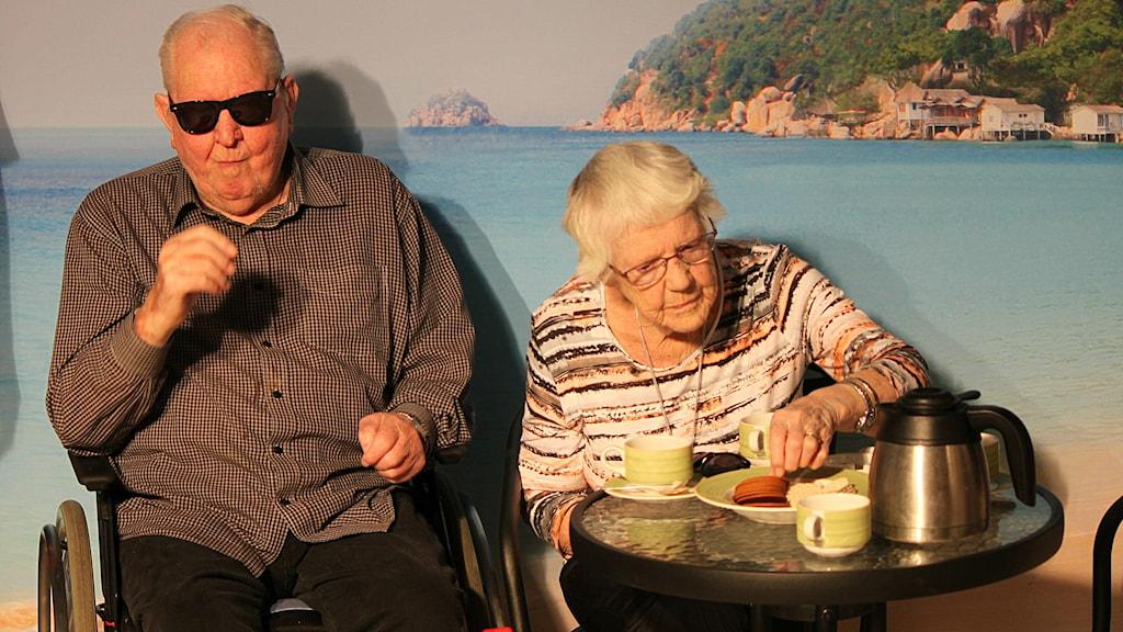 Äldre man och kvinna ser ut som om de sitter vid stranden och fikar