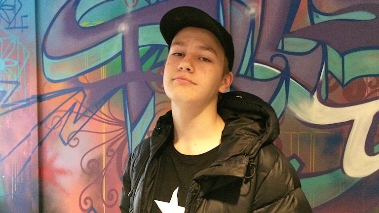 Ung kille med keps står framför graffitivägg