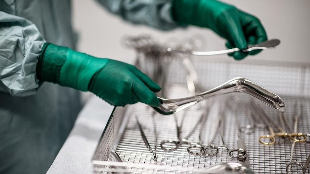 Person med gröna plasthandskar håller i operationsinstrument