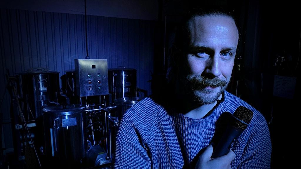 Man med mustasch håller mikrofon mot bröstet och är upplyst i blått ljus.