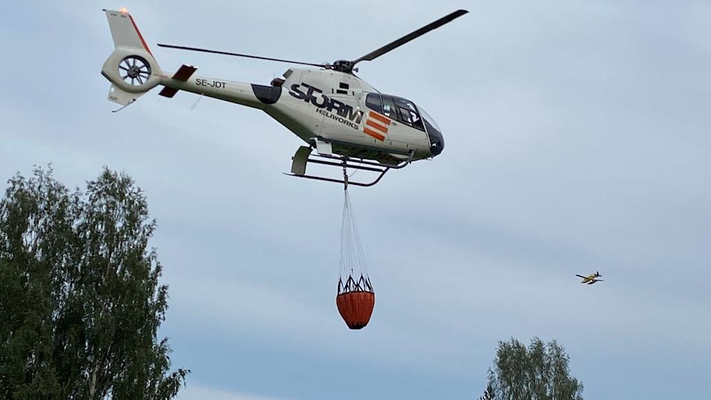 En helikopter vattenbombar en skogsbrand.