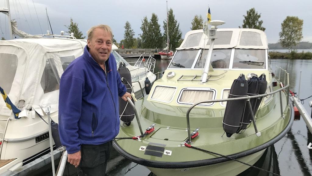 Anders Nilsson framför båten.
