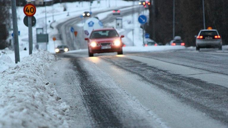 Personbilar kör på vinterväg med is och sand