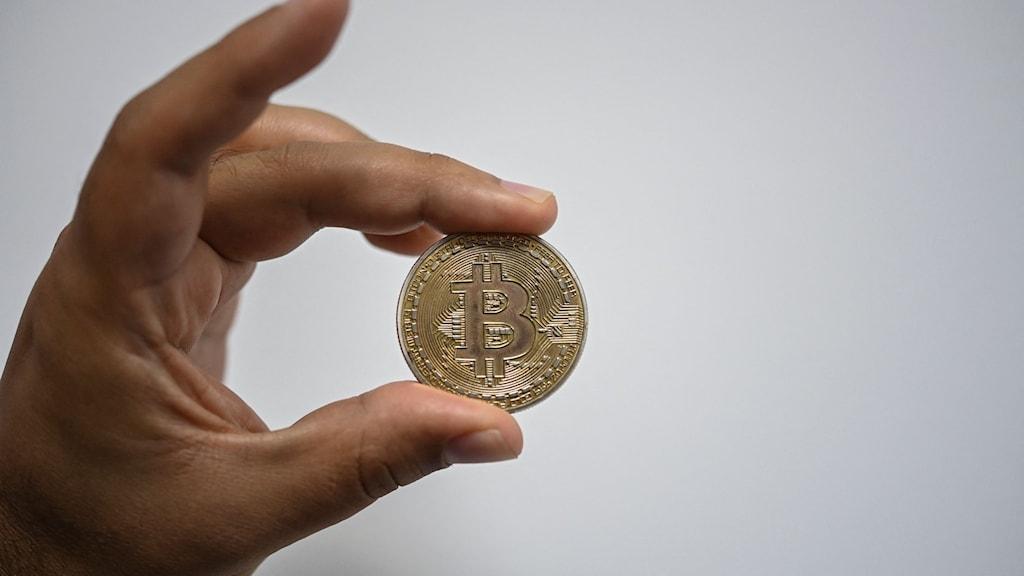 En guld peng med ett B på hålls upp mellan tumme och långfinger