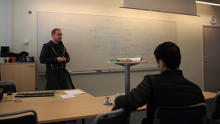En lärare står framför en vit tavla i ett klassrum. I förgrunden en mörkhårig pojke bakifrån