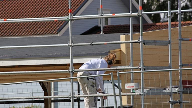 Byggarbetsplats med kvinnlig byggarbetare och byggställningar
