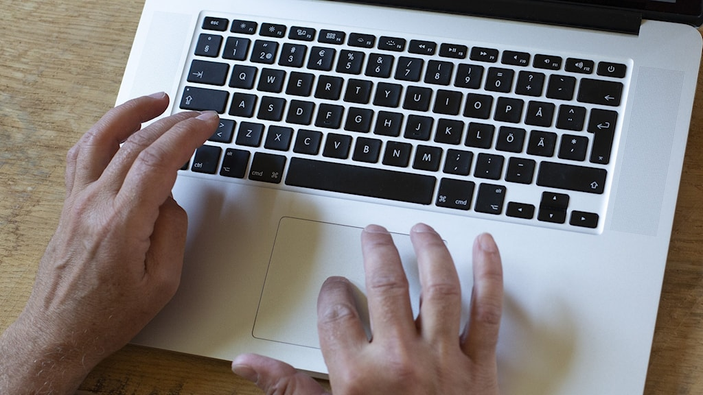 Två äldre händer som skriver på ett datortangentbord