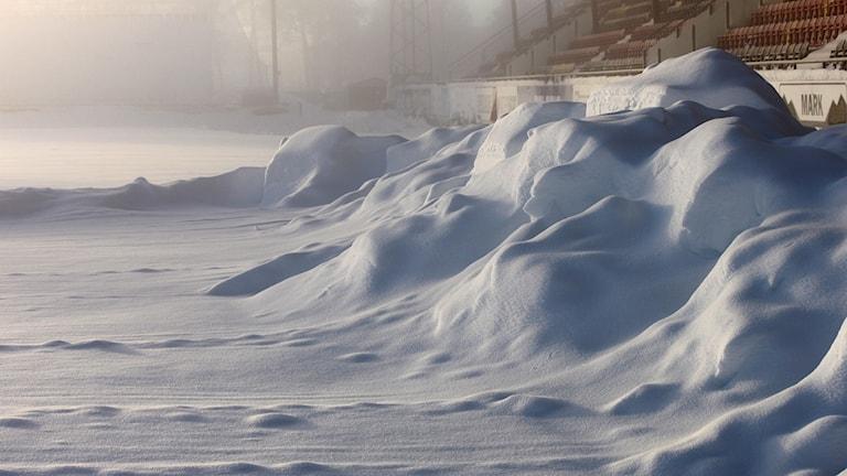 Snötäckt fotbollsplan och publikläktare på Jämtkraft Arena Östersund