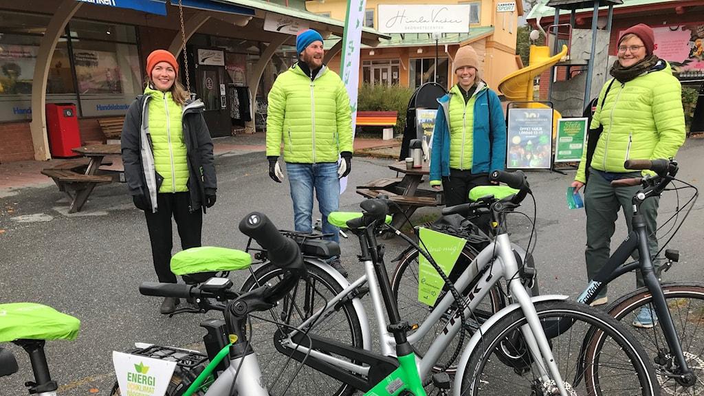 Fyra personer står utomhus i molnigt väder framför ett gäng cyklar. Samtliga är klädda i ljusgröna kläder.