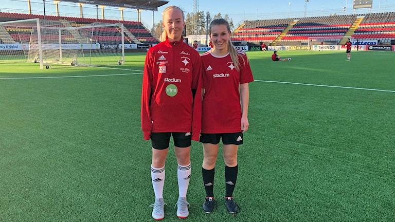 Två unga fotbollstjejer i röda tröjor och svarta shorts